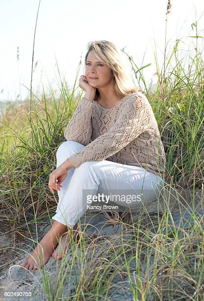 Mature (55+) woman sitting in dunes
