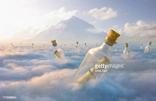 messages in bottles floating in clouds - social media stock illustrations