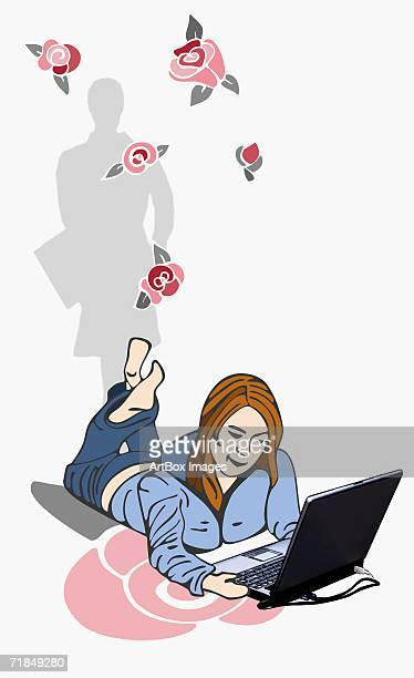 Mid adult woman lying on the floor and using a laptop