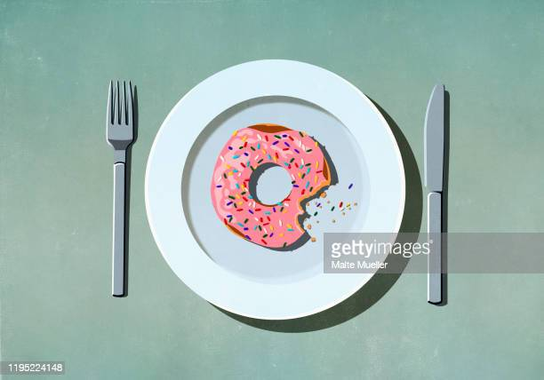 missing bite from pink donut with sprinkles on plate - food and drink stock illustrations