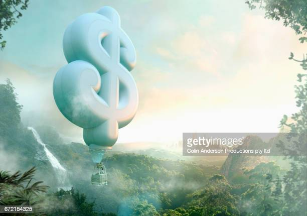 Mixed Race man floating in dollar sign hot air balloon