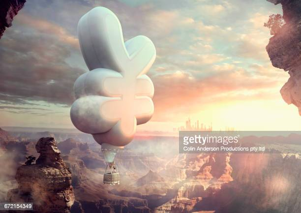 Mixed Race man floating in yuan hot air balloon at sunset