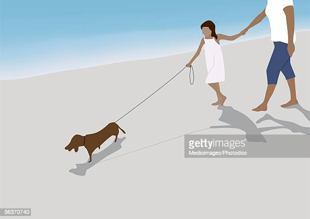 Mother and her daughter walking their dog on the beach