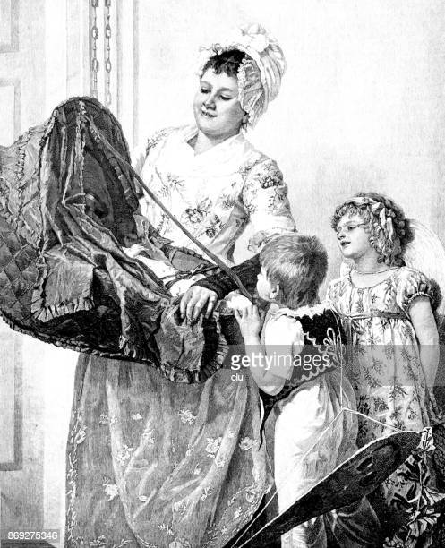 Mother shows the newborn baby in a carrying basket to the older children