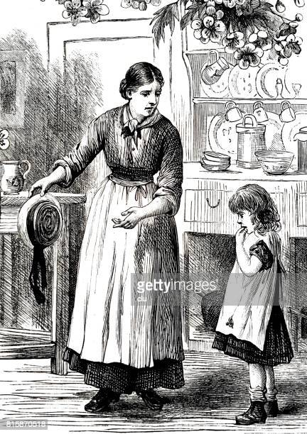 Mother talking to her daughter in kitchen, holding a hat
