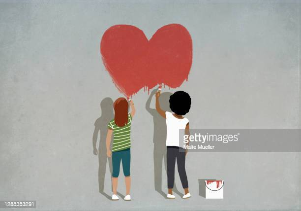 multiethnic girls painting red heart on wall - full length stock illustrations