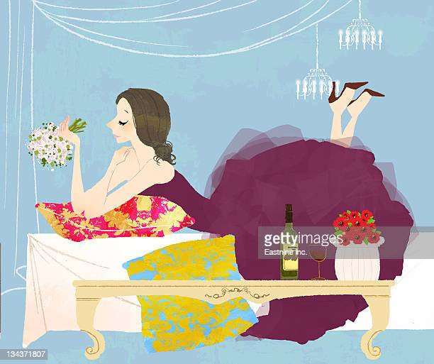 newlywed woman laying on bed holding bouquet of flowers