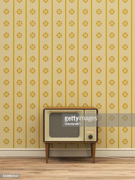 Old television in front of yellow patterned wallpaper