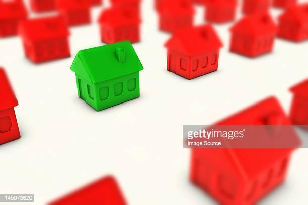 one green house amongst many red houses - housing development stock illustrations