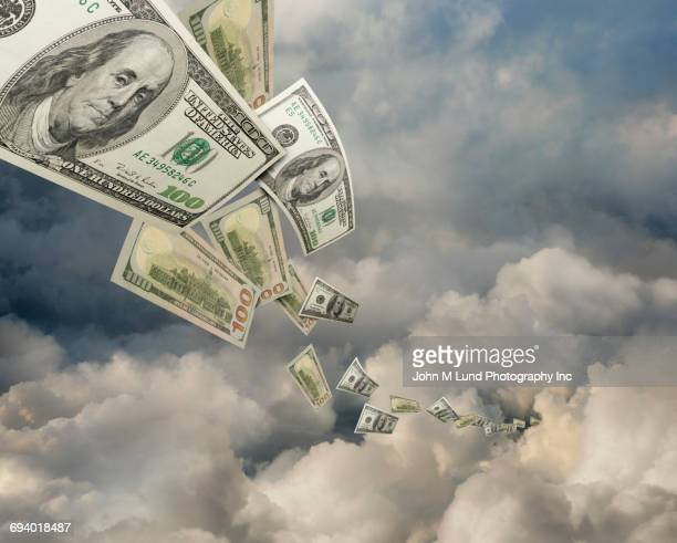 one hundred dollar bills flying in clouds - cash flow stock illustrations, clip art, cartoons, & icons