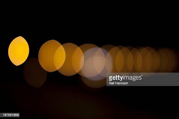 Orange circular light pattern against a black background