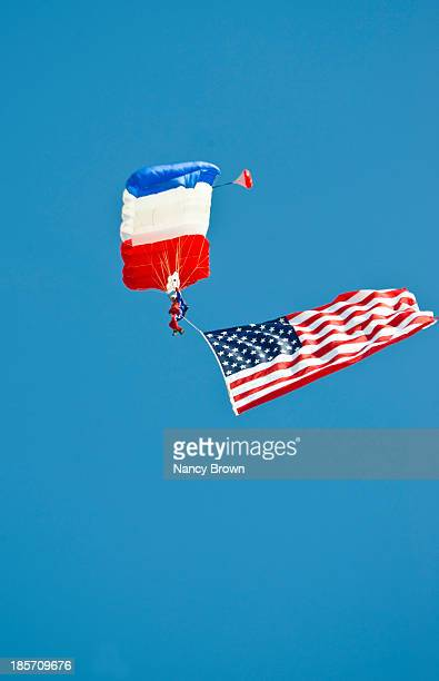 parachutist in air show in oshkosh wis. - all european flags stock illustrations