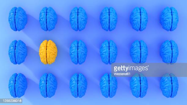 pattern of rows of blue colored human brains with single yellow one - in a row stock illustrations