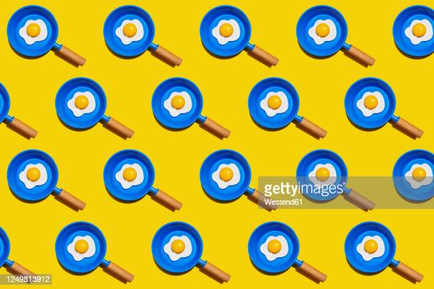 ilustrações, clipart, desenhos animados e ícones de pattern of rows of fried eggs on blue pans against yellow background - frito