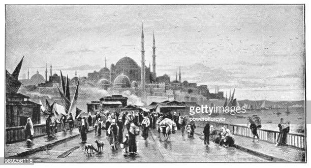 people crossing galata bridge with yeni cami on the skyline in istanbul, turkey - ottoman empire - ottoman empire stock illustrations