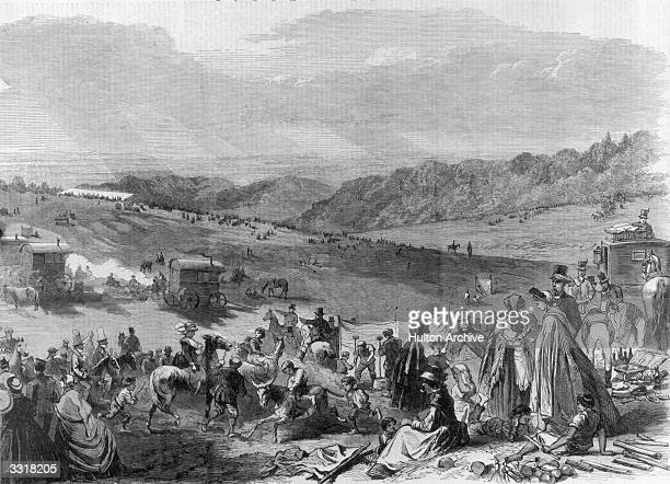 People gathering on the Epsom Downs on the morning of a Derby day. Gypsies and stall-holders are setting up their pitches.