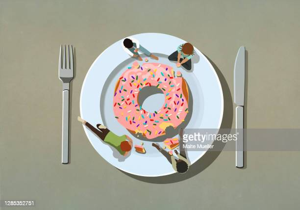 people indulging in large sprinkle donut on plate - scale stock illustrations