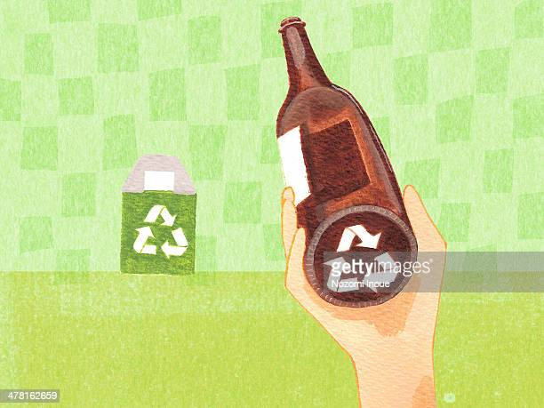 A person looking at the bottom of a bottle to see if it is recyclable