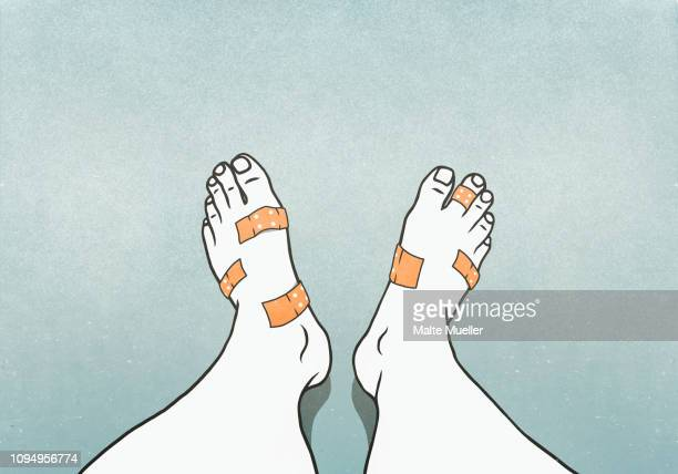 Personal perspective man with bandages covering blisters on feet