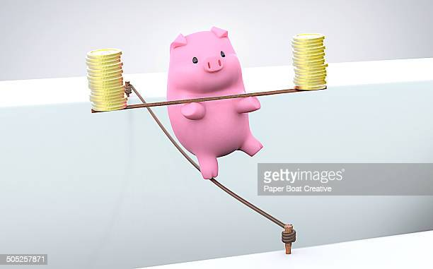 Piggy Bank on a tight rope balancing gold coins