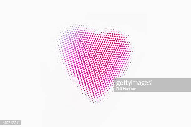 Pink and purple spotted heart against a white background