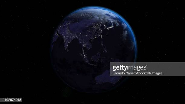 planet earth showing oceania in night time with city lights. - satellite view stock illustrations