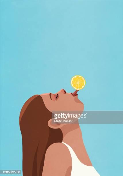 playful young woman balancing lemon on tongue - adult stock illustrations