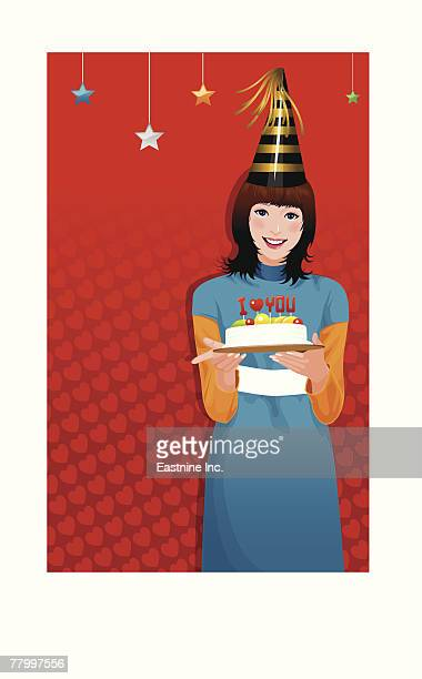 Portrait of a woman holding a cake and smiling