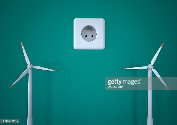Power socket with wind turbines against green background, close up