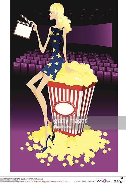Profile of woman sitting on carton of popcorn, holding film slate