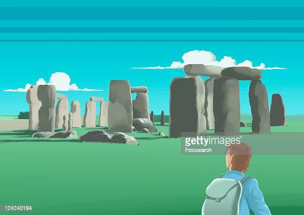 ilustrações de stock, clip art, desenhos animados e ícones de rear view of a young man looking at old ruins, stone circle, salisbury plain, stonehenge, england - megalith
