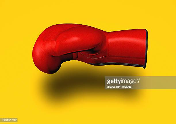 red boxing glove on yellow background - boxing glove stock illustrations