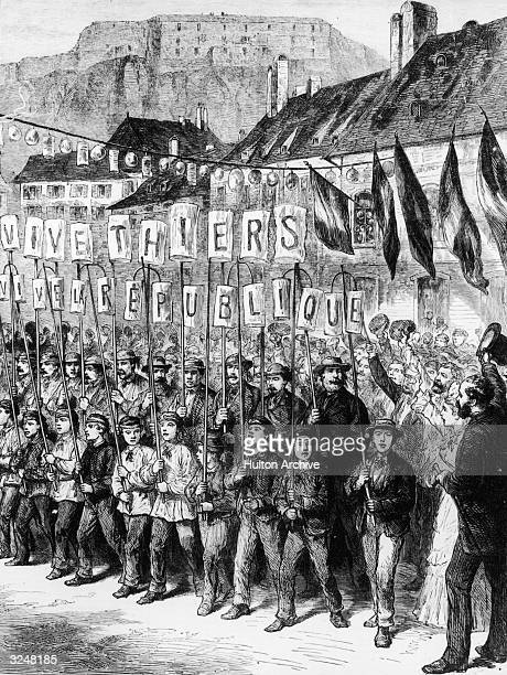 Rejoicing in the fortress town of Belfort upon the withdrawal of the beseiging Germans after the Franco-Prussian War. The citizens hold up poles...