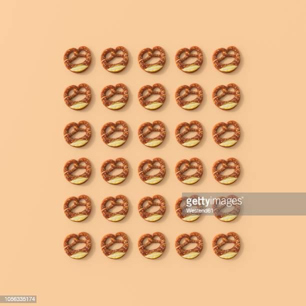 3d rendering, rows of pretzels on orange background - pretzel stock illustrations, clip art, cartoons, & icons