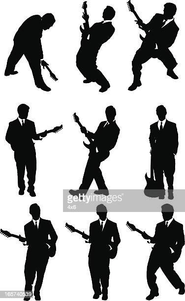 rock star playing guitar in a business suit - guitarist stock illustrations