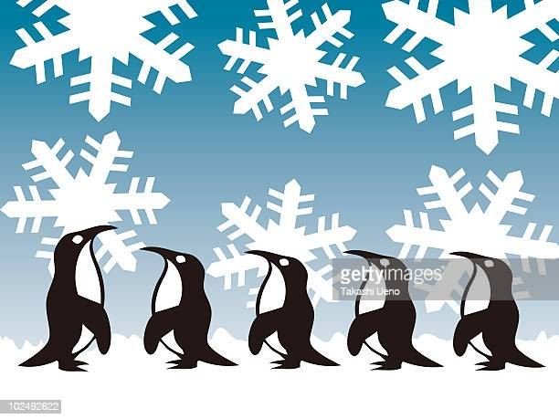 A row of penguins in a row on a snow flake backdrop