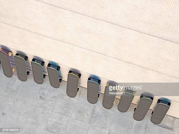 Row of skateboards leaning on concrete wall, 3D Rendering