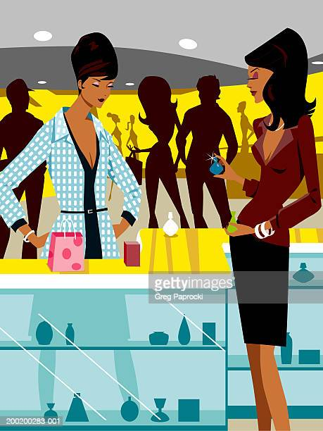 Salesclerk assisting woman with perfume in retail store