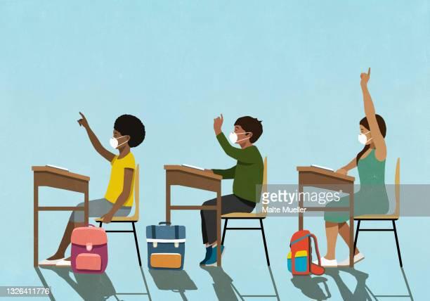 school children in face masks raising hands at classroom desks - klassenzimmer stock-grafiken, -clipart, -cartoons und -symbole