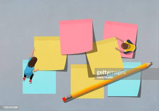 schoolchildren arranging large multicolor adhesive notes - brainstorming stock-grafiken, -clipart, -cartoons und -symbole