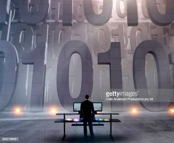 Security officer at control panel guarding binary code