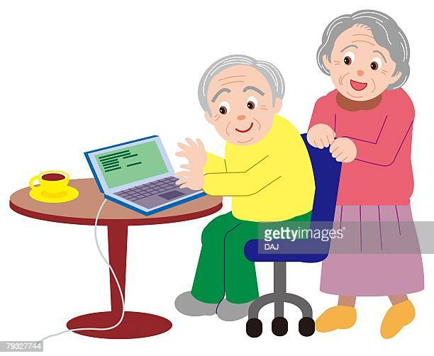 Senior man and woman looking at laptop on the table together