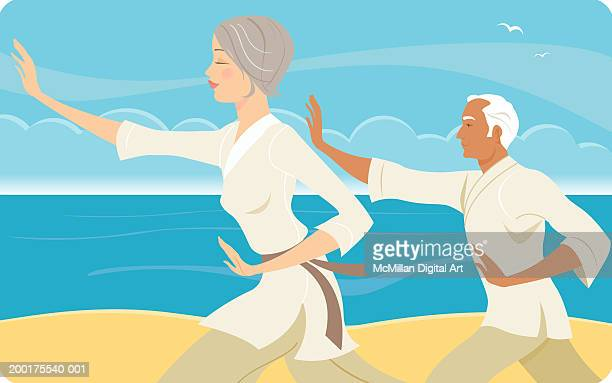 Senior man and woman practicing tai chi on beach, side view