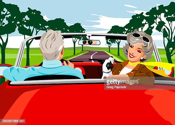 Senior man and woman riding in convertible with dog