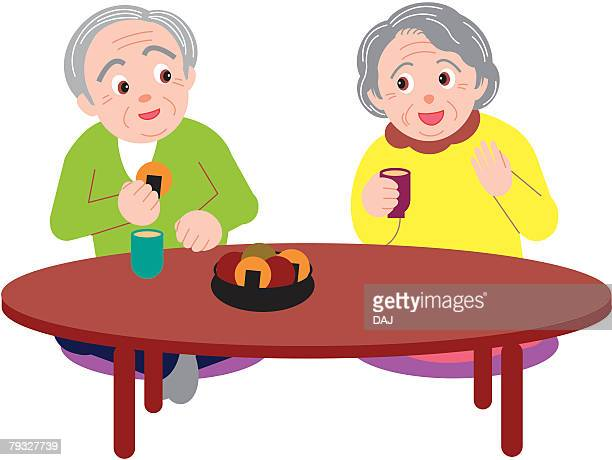 Senior man and woman talking and eating rice crackers, front view