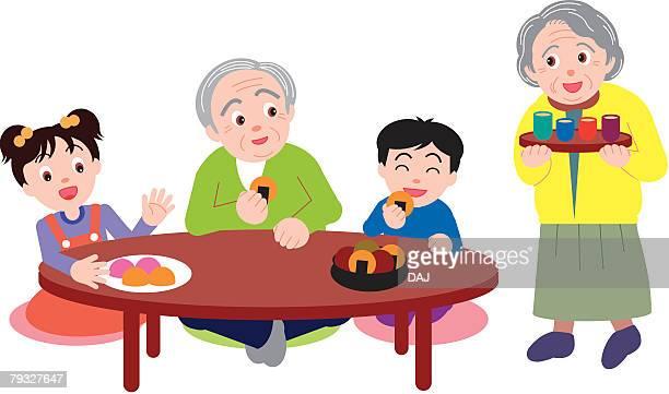 Senior man sitting at table with grandchildren, senior woman bringing cups of tea