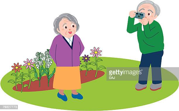 Senior man taking a picture of senior woman, front view