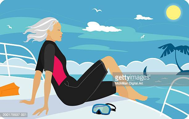 Senior woman in wetsuit sitting on boat deck, side view