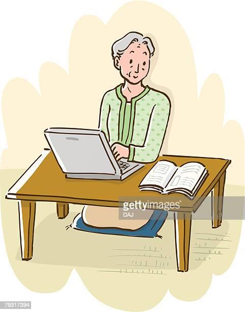 Senior woman using laptop, looking at operating manual, high angle view