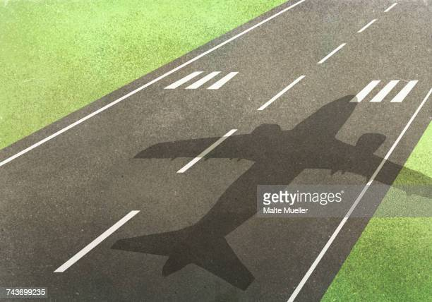 Shadow of airplane on runway amidst field